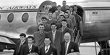 Sebuah foto hitam-putih dari beberapa orang memakai jas dan mantel di tangga pesawat.