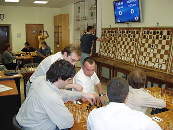 Photo of a room with several chessboards on tables, groups of men playing around two of them. On the wall, several large demonstration chessboards