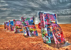Psychedelia - A row of buried Cadillacs painted in rainbow hues.