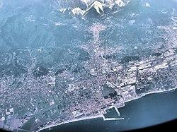 Het gebied rond Carrara, gezien vanuit een vliegtuig dat op 10.000 meter hoogte vliegt.  De stad staat bovenaan de foto, het dichtst bij de marmergroeven, de witte markeringen op de bergen.