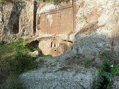 Façade d'une tombe creusée dans la falaise avec une fausse porte en forme de T gravée dessus.