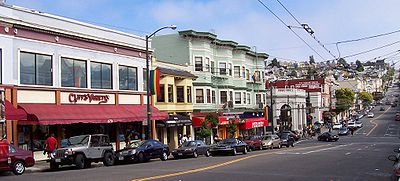 Stores on Castro Street near the intersection with 18th. Rainbow flags, which are commonly associated with gay pride, may be seen hung on streetlights along the road.