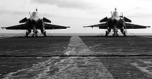 Landscape photograph of two jet parked side-by-side on carrier deck, with faint white line running down the middle.