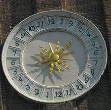 Decorative clay/stone circular off-white sundial with bright gold stylized sunburst in center of 24 hour clock face, one through twelve clockwise on right, and one through twelve again clockwise on left, with J shapes where ones' digits would be expected when numbering the clock hours. Shadow suggests 3 PM toward lower left.