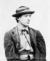 A young man looking sour and facing right. He is dressed in a jacket, bow tie, and wide-brimmed hat, and his shirt is partially unbuttoned.