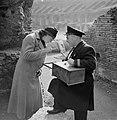 Dame (Nell Langlais) kijkt met een loep naar camees van een verkoper bij het Co, Bestanddeelnr 191-1234.jpg