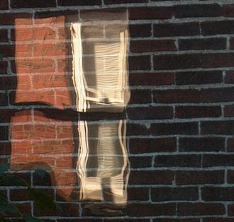 Architectural glass - The uneven surface of old glass is visible in the reflection on this window pane.