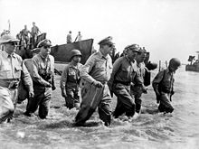 A group of men wading ashore. With General MacArthur is Philippine President Sergio Osmeña and other US and Philippine Generals.