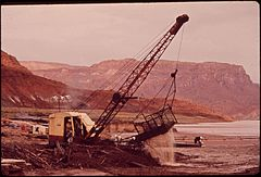Dragline Shovel Scoops Up Oil - Laden Debris from Log Boom on San Juan River near Lake Powell, 10-1972 (3814161593).jpg