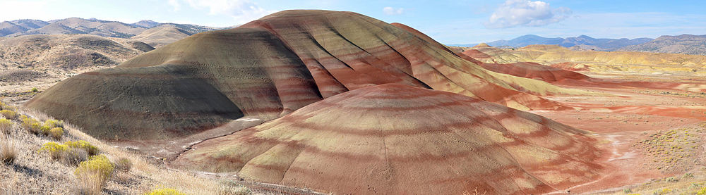 Multicolored rock strata in shades of red and yellow comprise a set of low, bare, rounded hills