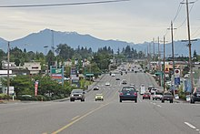 A wide suburban street with turn lanes, seen against strip malls, utility poles, and mountains in the background.
