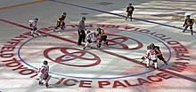 In the middle of a large red circle with the Toyota logo, lit partially by sunlight shining through the roof above, two hockey players from different teams are attempting to take control of the puck beneath them. The referee, in a black and white vertically striped shirt with an orange band around his upper right arm, stands off to their left. Around the edges of the circle are the two players' teammates, some just beginning to skate into the circle.