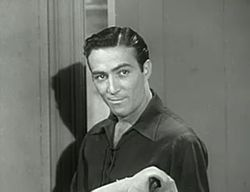 A dark-haired man wearing a dark shirt