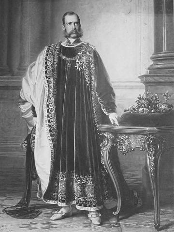 Franz Joseph in the regalia of the Order of the Golden Fleece, with the Bohemian Crown Jewels next to him. Painting by Eduard von Engerth for the Bohemian Diet, 1861. Franz Joseph of Bohemia 1861.jpg