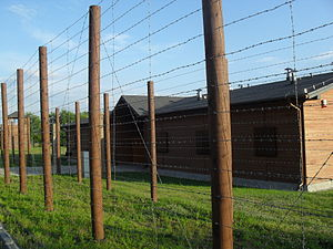 Dębica - Reconstructed camp barracks with a watchtower and the barbed-wire fence in the village of Pustków
