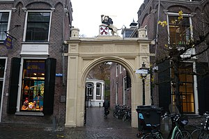 Burcht van Leiden - Southern gate to the Burcht with historic timeline 1203, 1420 and 1574 in Latin. Now facing a busy shopping street.