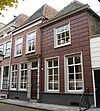 foto van Twee huizen, onder afzonderlijke schilddaken, het linkse met een lijstgevel in schoon werk en met een geblokte ingangsomlijsting, het rechtse gebosseerd roze gepleisterd