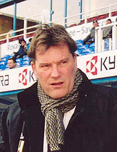 A middle-aged white man, in a jacket with a scarf wrapped around his neck
