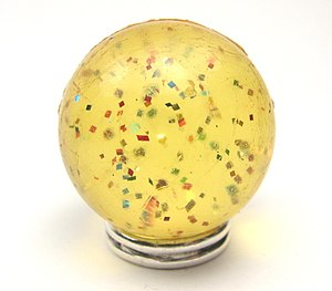 Super Ball - A Super Ball containing particles of glitter, resting on a base. The transparent rubber has yellowed with age.