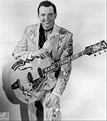 A dark-haired man wearing an elaborately-patterned suit and holding a guitar