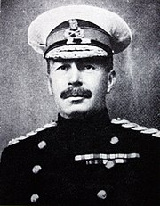 Monochrome portrait of officer in cap and uniform. Cap has white cover. Medal ribbons and shoulder braid of Flag Officer visible.