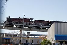 "The lower half of the photograph shows industrial office buildings, with a small label ""T-4"" in one corner.  Above this runs a steel construction carrying an elevated rail system, with an emergency exit walkway.  Mounted on the track is a red steam locomotive with two small wheels and three big wheels raised slightly above the track.  Above the middle of the three big wheels is a curved sign that says ""Hogwarts Castle"".  Under the train are sets of much smaller wheels resting directly on the track."