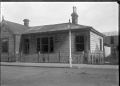 House after a fire, showing damage to walls, windows and roof, at Petone. ATLIB 289858.png