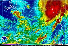 Colorized infrared satellite image of a hurricane. The storm, is in the top right portion of the image and has a poorly defined eye. A red mass, depicting strong convective activity, is present along the eastern side of the storm.