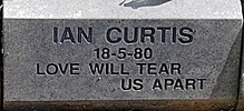 "A gray stone marker with some grit and sand on it. It has an inscription carved into it in sans-serif capital letters reading ""Ian Curtis, 18-5-80, Love Will Tear Us Apart"""