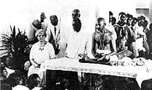 A seated Ida Scudder and Mahatma Gandhi, with other men