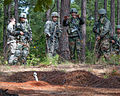 Indian Army Maj. Prashant Mishra explains how his soldiers deal with unexploded munitions to Sgt. Micheal Mark, a U.S. Army combat engineer.jpg