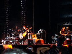 Two guitarists, a drummer and a keyboard player are performing on an orange lit stage in front of an audience. Various pieces of equipment surround the group. The stage features a black backdrop with two strips of vertical lights.