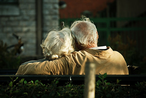 It's all about love: And older couple sitting together on a park bench.