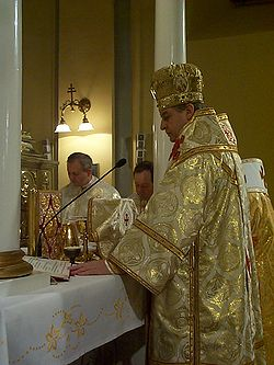 Bishop celebrating Divine Liturgy in Greek-Catholic church in Presov, eastern Slovakia. Another bishop stands to his immediate right (white omophorion visible), and two married priests stand to the side (facing camera).