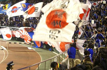 Fans waving flags in support of the Japanese national team. Japan national football team fans with rising sun flag.JPG