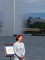 Prime Minister Julia Gillard standing in front of the Captain Cook Memorial Jet during the 2013 National Flag Raising and Citizenship ceremony