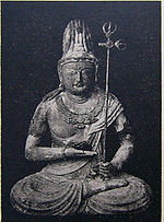 Front view of a statue in lotus position. The palm of the right hand is turned upward and held in front of the stomach. The left hand, close to the right foot, is holding a long pole with decorations at the end resembling a trident.