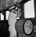 Kapitein in wit uniform met verrekijker in de stuurhut staande bij de scheepstel, Bestanddeelnr 255-4954.jpg