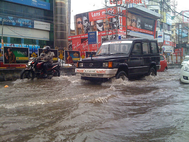 A police jeep driving through a waterlogged street in the monsoon in Kerala