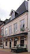 foto van Huis met afgeknotte gevel met zandstenen banden en beeldhouwwerk in het fries en met gewijzigde onderpui