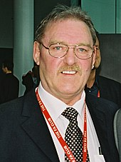 Kevin Beattie wearing a dark jacket, a white shirt, and black-and-white polka dot tie