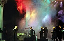 Faraway image of a female blond singer wearing a black robe with a crucifix and singing to a microphone she holds in her hand. Behind here several African-American dancers dressed similarly can be seen. The staged is filled with a colored smoke and some drums and a cross can be seen.