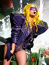 A young woman on stage. She wears a bright yellow wig, a purple shiny jacket with shoulder pads, and matching purple sunglasses with a leotard and stockings.