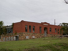 A red brick building with broken windows and lots of vegetation.
