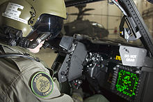 Pilot sitting in cockpit looking at controls