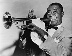 A picture of Louis Armstrong. Short-haired black man in his fifties blowing into a trumpet. He is wearing a light-colored sport coat, a white shirt and a bow tie. He is faced left with his eyes looking upwards. His right hand is fingering the trumpet, with the index finger down and three fingers pointing upwards. The man's left hand is mostly covered with a handkerchief and it has a shining ring on the little finger. He is wearing a wristwatch on the left wrist.