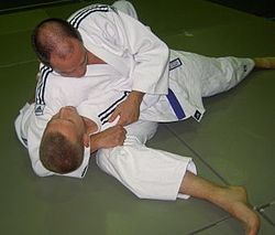Judoka demonstrating kesa gatame variation