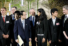 President George W. Bush and Japanese Prime Minister are on the right of a high school student. The high school student speaks. In the background are more high school students and important political figures.