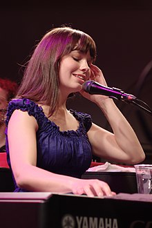A young brunette woman in a blue dress behind a keyboard and microphone.