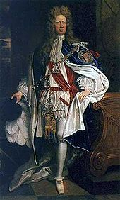 A man in robes of the Order of the Garter. The man is wearing white and red clothing, with a mantle adorned with a large badge.